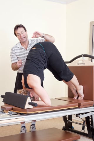 Norm teaching a STOTT PILATES client