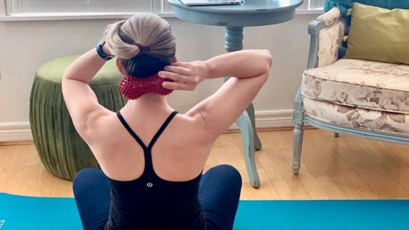 The Pilates instructor uses the Peanut Massage Ball to release tension in her neck, a great exercise for desk workers