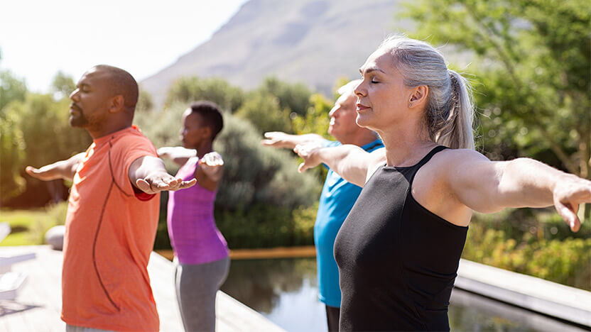 A group of exercise participants practice mindful breathing outside