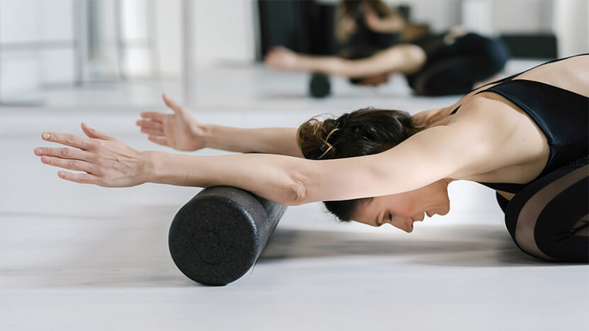 A woman relaxes and breathes on her Foam Roller in a Pilates class