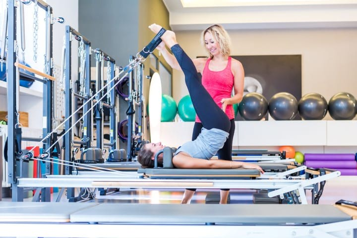 Claudia instructing a Pilates Reformer client