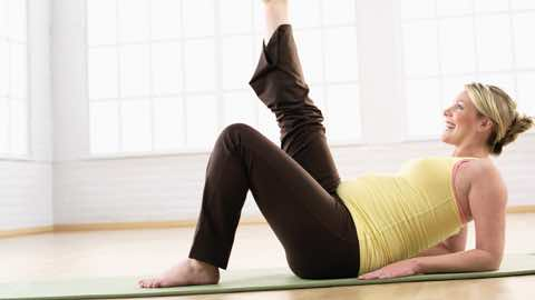 Woman stretching leg lying on Mat