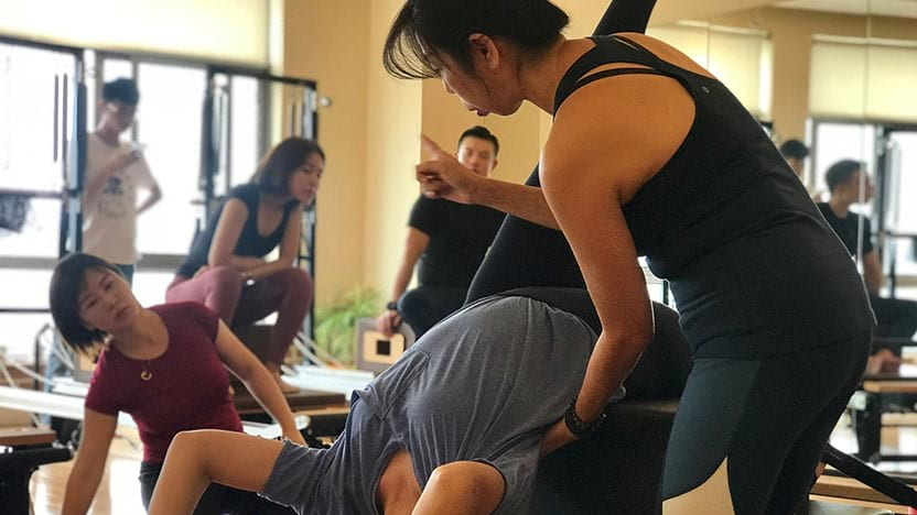 Patricia working with student on Reformer