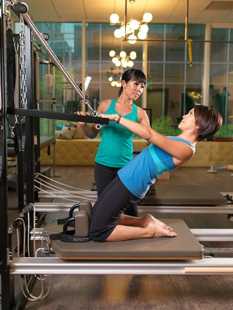 Cholthicha teaching Reformer Pilates to a client