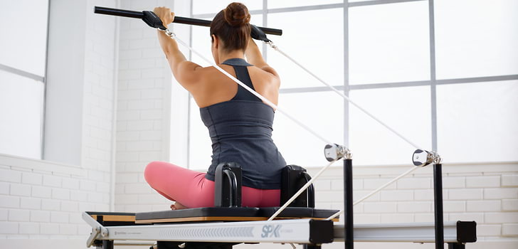 Woman exercising on a STOTT PILATES At Home SPX Reformer