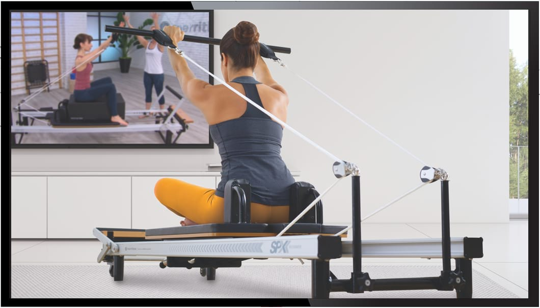 Woman working out on a Pilates Reformer while watching Merrithew Connect