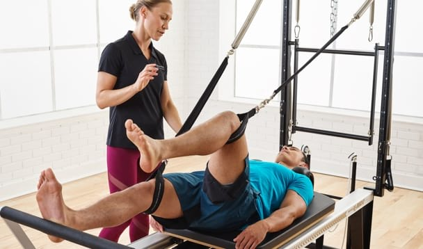Rehab instructor on helping client on a STOTT PILATES Reformer