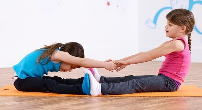 Kids stretching holding hands while seated on Mat