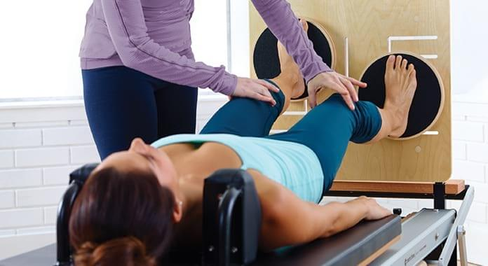Student lying back on Rehab Reformer with feet on Diskboard
